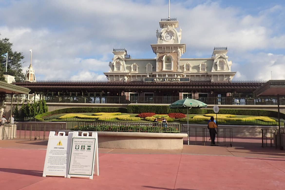 The Magic Kingdom Esplanade with the Walt Disney World Railroad Station and COVID-19 Safety Rule signage posted.