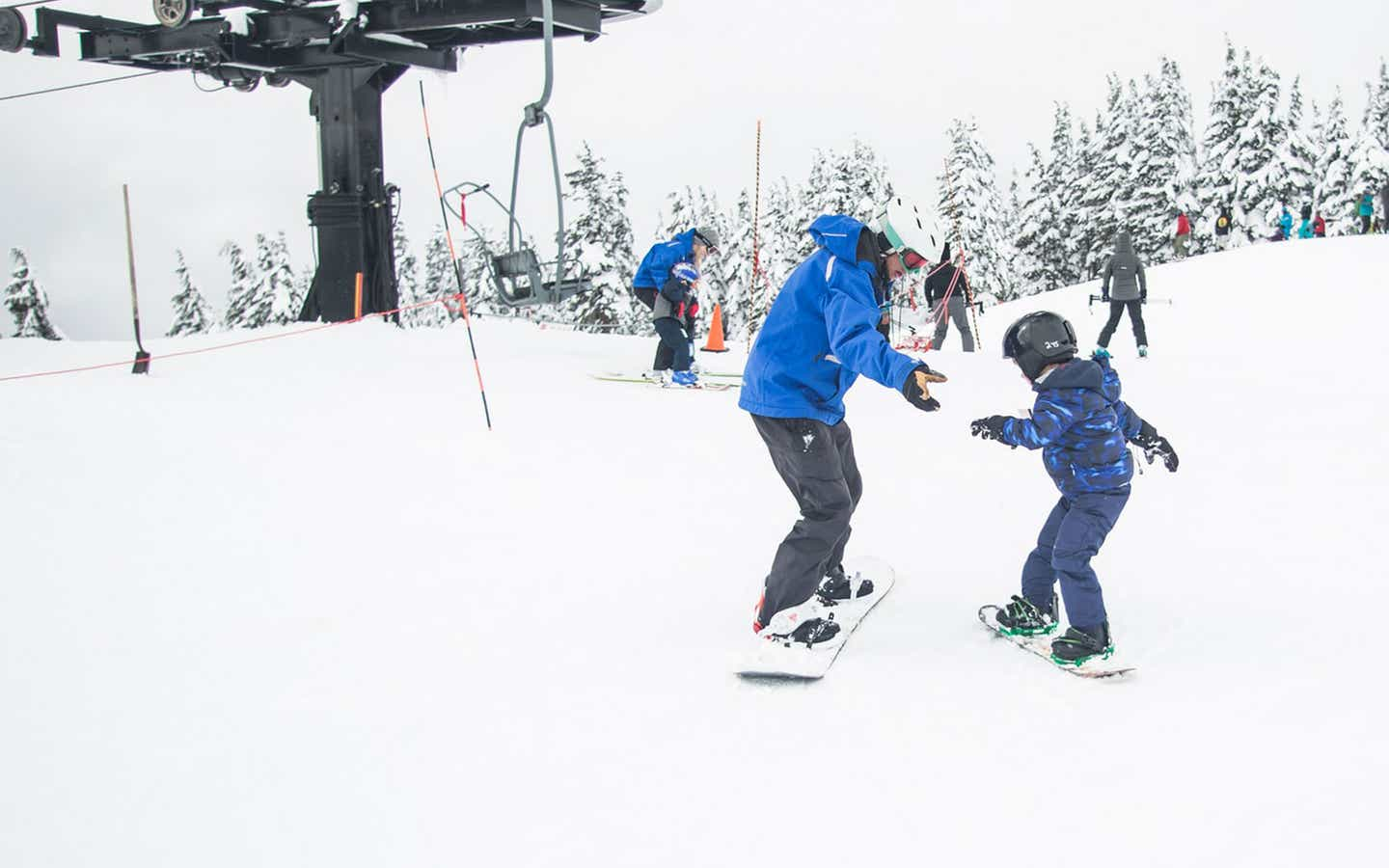 A man and child are learning to snowboard near a ski lift.