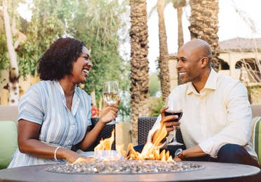 Man and woman sitting outside and holding glasses of wine at Scottsdale Resort in Arizona