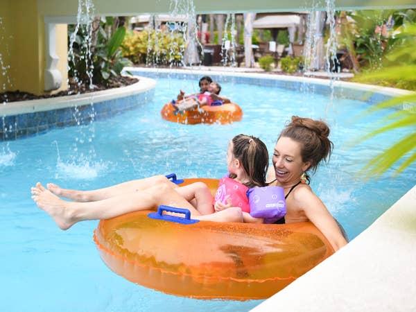 Three guests floating in lazy river at Orange Lake Resort near Orlando, Florida.