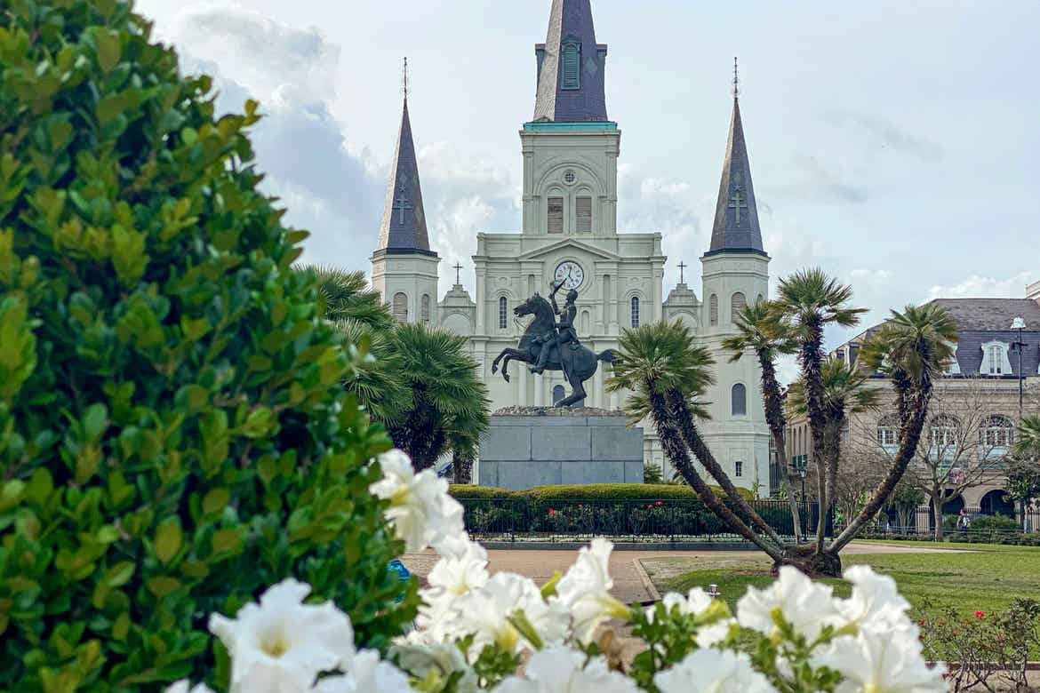 Jackson Square and the St. Louis Cathedral seen behind a floral foreground of greenery and white flowers.