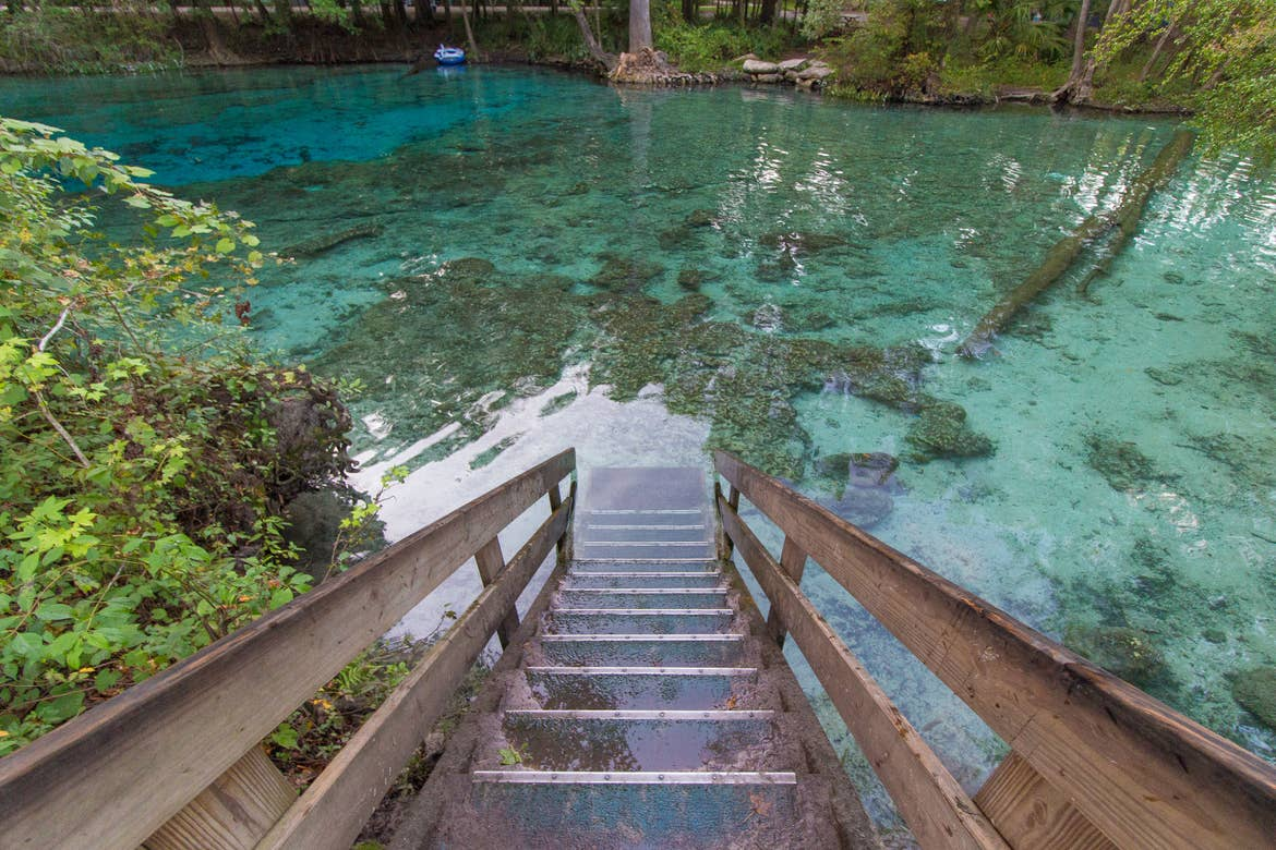 Stairs descending into crystal blue waters at Blue Spring State Park