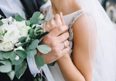 Closeup of bride and groom with wedding flowers and rings.