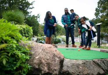 Family of five playing outdoor mini golf at Villages Resort in Flint, Texas.