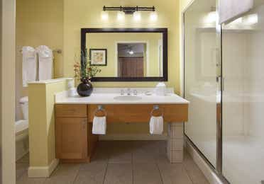 Bathroom with walk-in shower, sink with large mirror, and toilet in a one-bedroom villa at Lake Geneva Resort