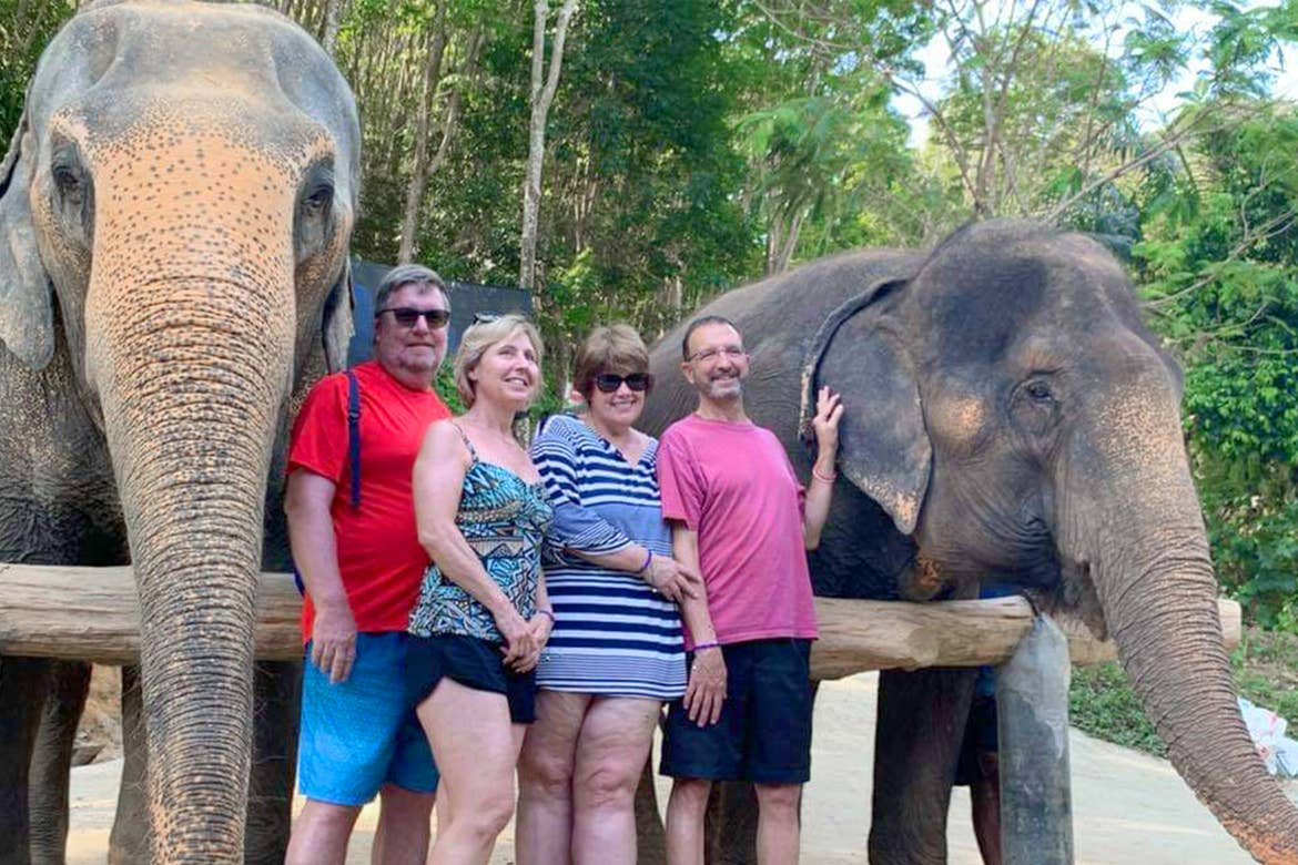 Two caucasian men and two women stand in front of two elephants near a wooden fence and jungle foliage in Phuket, Thailand.