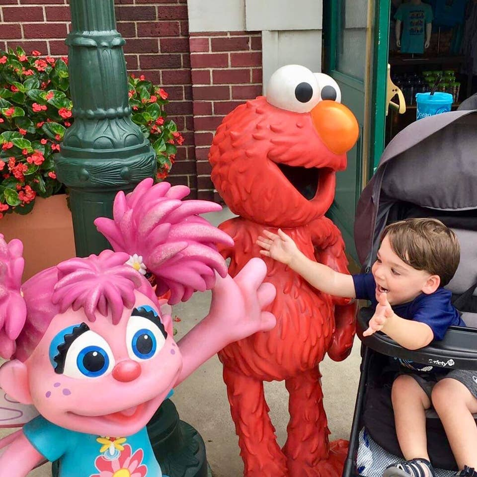 Dakota, Theresa's son, reaches from his stroller to embrace Elmo and Abby Cadabby outside Sesame Street Land.