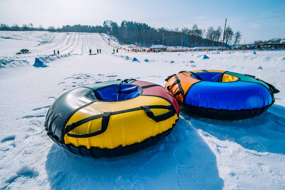 Two inflatable inner tubes at the bottom of a snowy incline.
