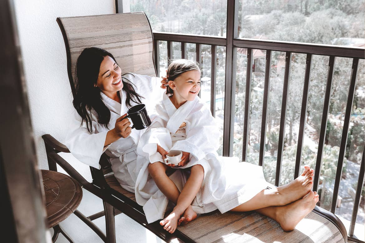 Featured contributor, Mia St. Clair (left), and daughter, Roux (right), enjoy time together wearing white robes and sipping tea on the patio at Orange Lake Resort in Orlando, FL.