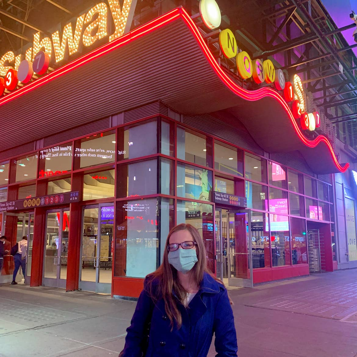 A Caucasian woman with long hair wears a pair of glasses, a safety mask and a jacket outside of the Times Square subway station in New York City at night.