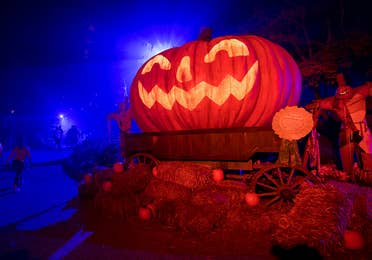 An oversized Jack O' Lantern sits on bales of hay at night.