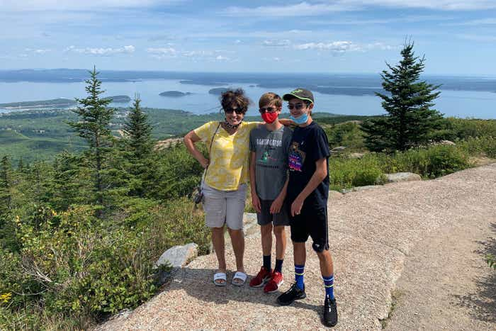 Author, Jennifer Probst (left), and her sons (middle and right) stand on the edge of the Acadia National Park hiking trail while wearing their masks.