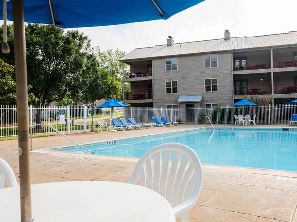 Outdoor lodge pool with view of property building at Villages Resort in Flint, Texas