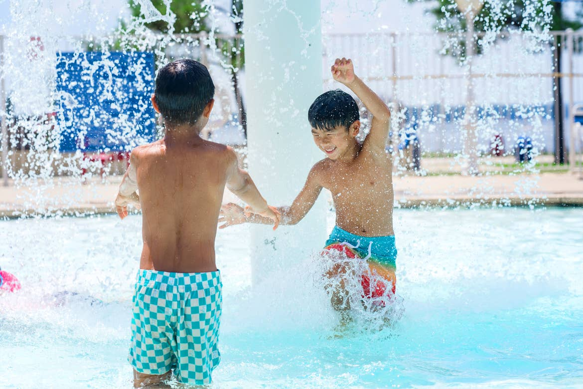 Two young, Asian boys wear multicolored swim trunks while playing under an outdoor pool fountain.