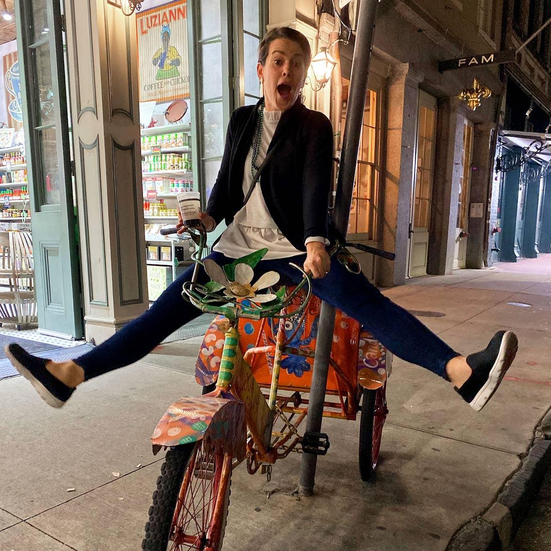Author, Jenn Harmon, rides a stationary bike decorated on Bourbon Street.