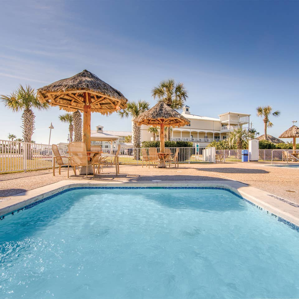 Outdoor pool surrounded by palm trees at Galveston Seaside Resort.
