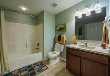 Bathroom with vanity and bathtub in a three-bedroom ambassador villa at the Holiday Hills Resort in Branson Missouri.