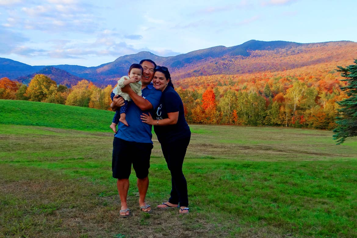 An Asian Pacific Islander toddler (left) is held by an Asian Pacific Islander man (middle) standing near a woman (right) surrounded by lush fall foliage.