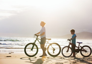 Adult and young child pushing bicycles on the beach