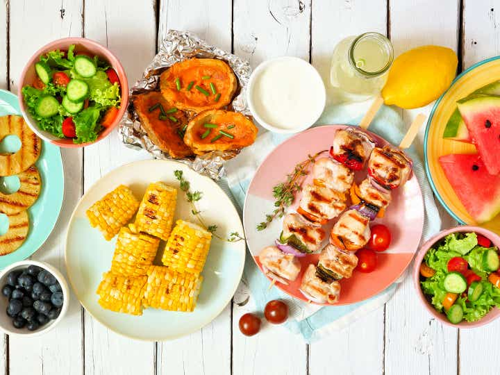 An array of grilled food on a picnic table