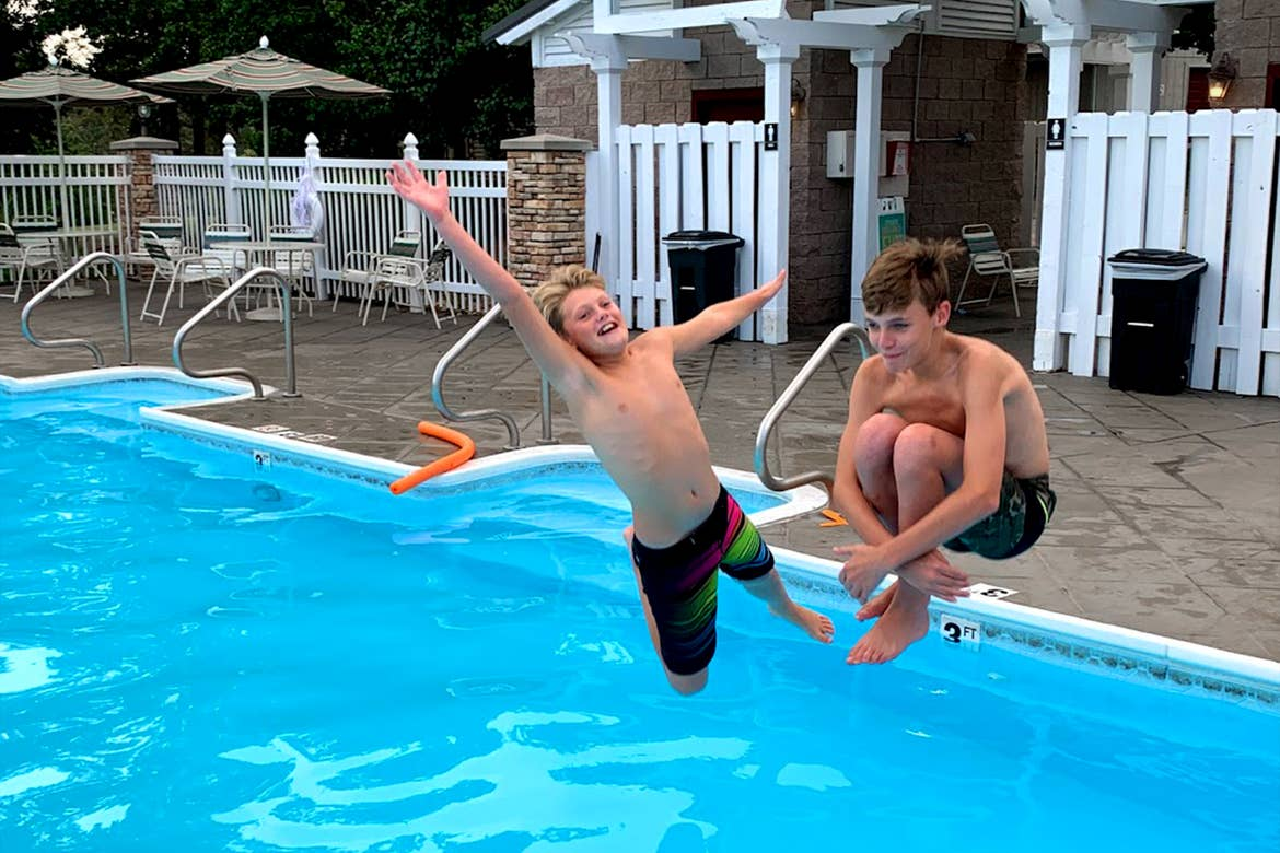 Two boys jump into an outdoor pool.