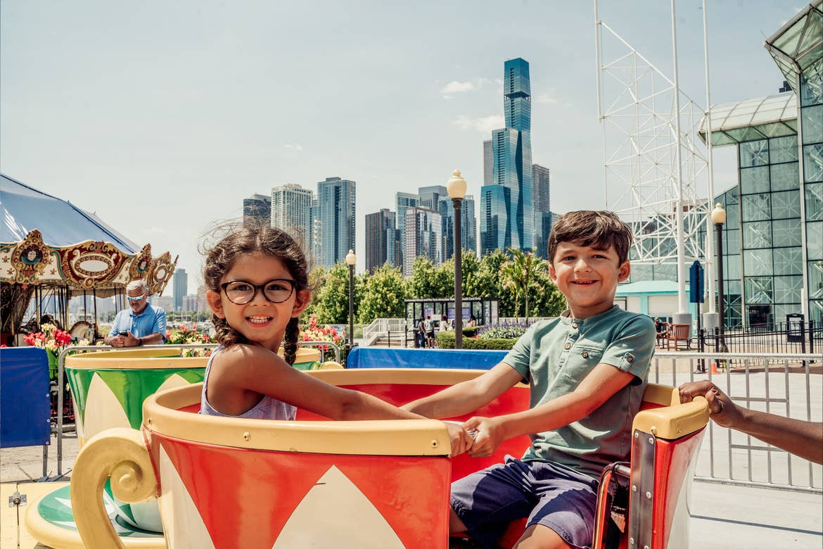 A young girl with glasses (left) and a young boy (right) sit in a spinning teacup ride outdoors.