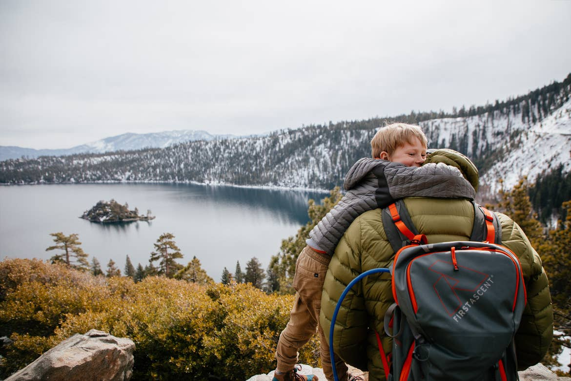 A young boy hugs his fathers shoulders at Emerald Bay State Park with a gorgeous forest as a backdrop.