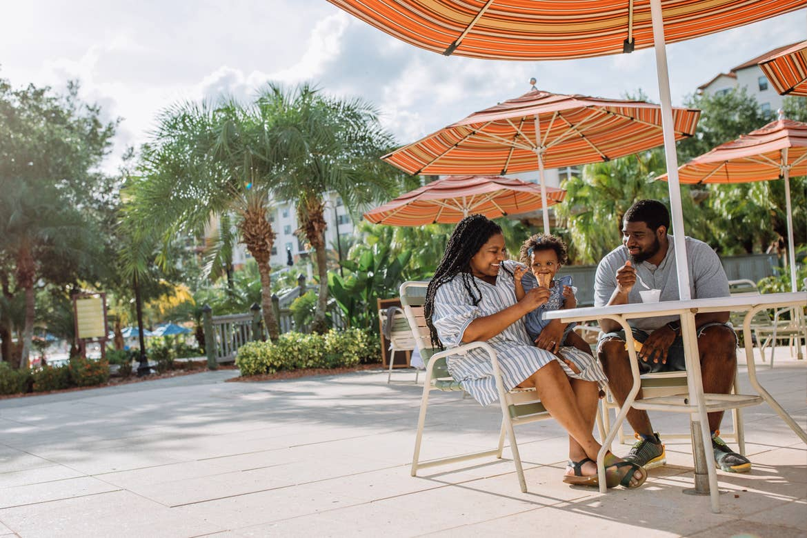 Krystin Godfrey (left) helps her daughter, Creed (middle) eat an ice cream cone with husband, Phillip (right) in River Island at our Orange Lake Resort located in Orlando, FL.
