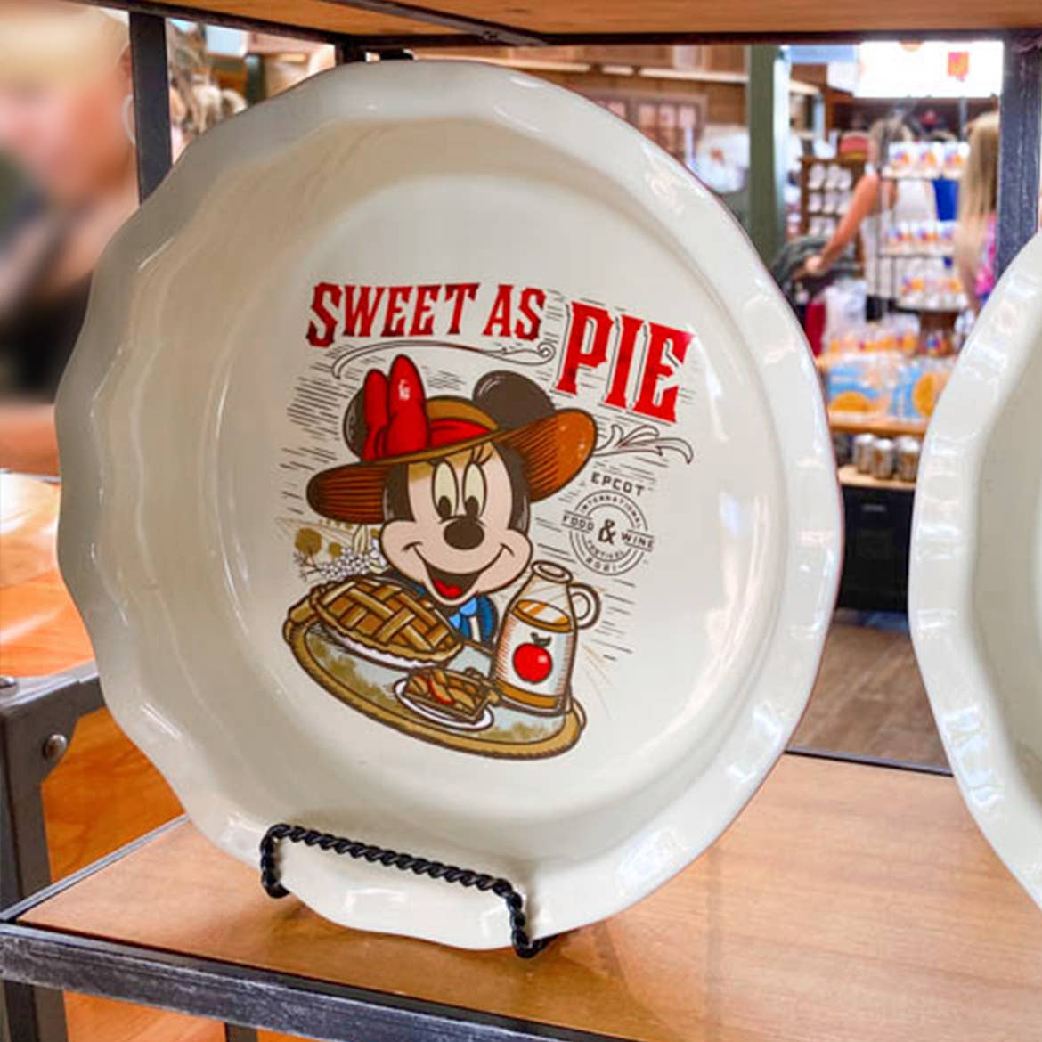 A ceramic pie dish featuring Minnie Mouse in a sunhat reads, 'Sweet as Pie' as it stands propped on a shelf.