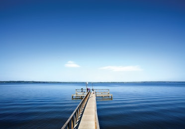 View of a lake with a long dock at Lake O' the Wood Resort in Flint Texas.
