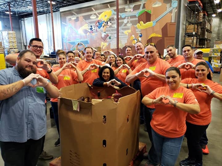 A group of volunteers at Second Harvest food bank in Orlando, FL making heart-shaped hand gestures
