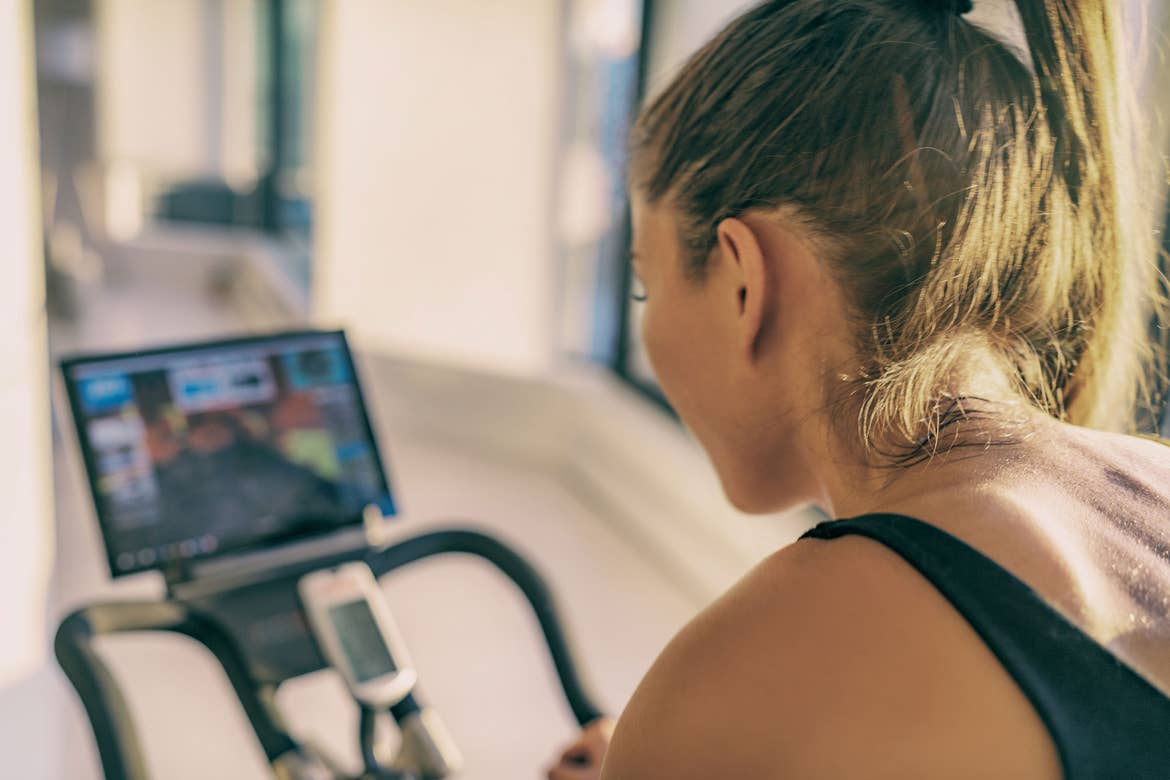 A woman rides an exercise bike while watching a virtual cycle class.