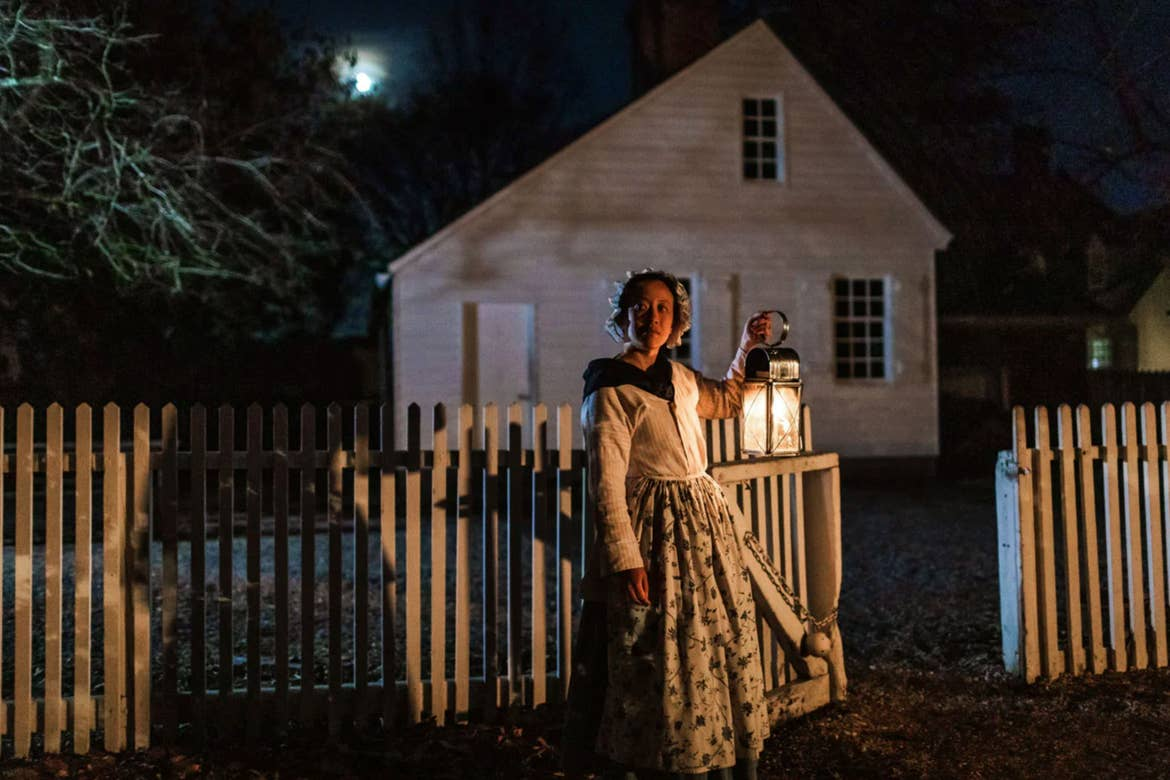 A woman in period costume stands outdoors at night holding a lantern.