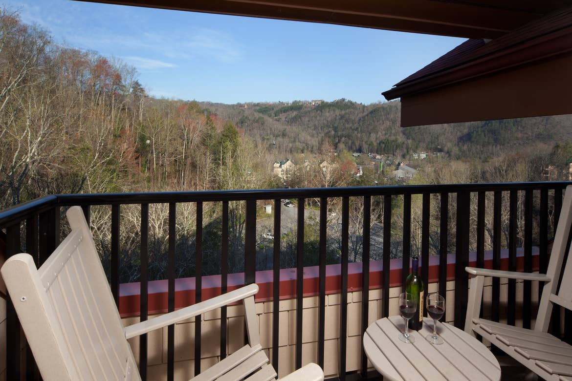 A pair of wooden rocking chairs placed on a balcony near a wooden table holding a green wine bottle, and two glasses of wine overlook the Smoky Mountains.