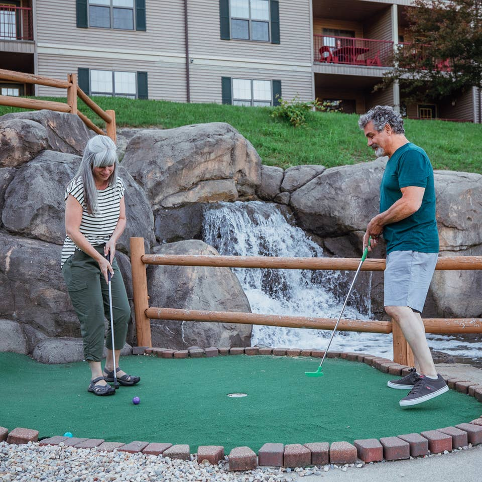 A couple playing mini golf at Oak n' Spruce Resort in South Lee, Massachusetts.