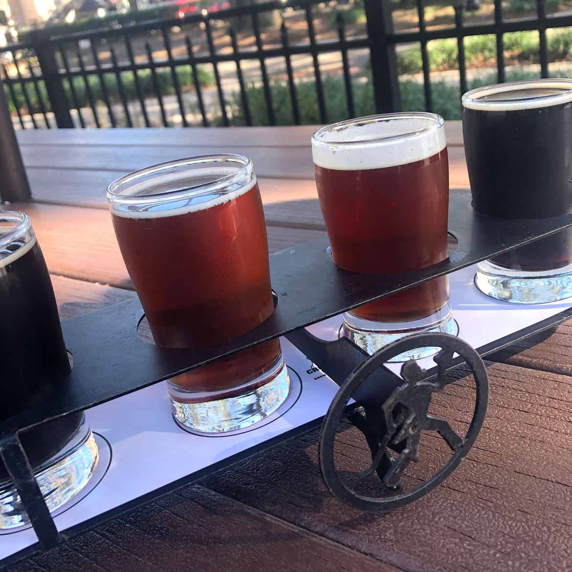 A beer flight with an iron 'Crooked Can' logo stand placed outside on a wooden plank table.