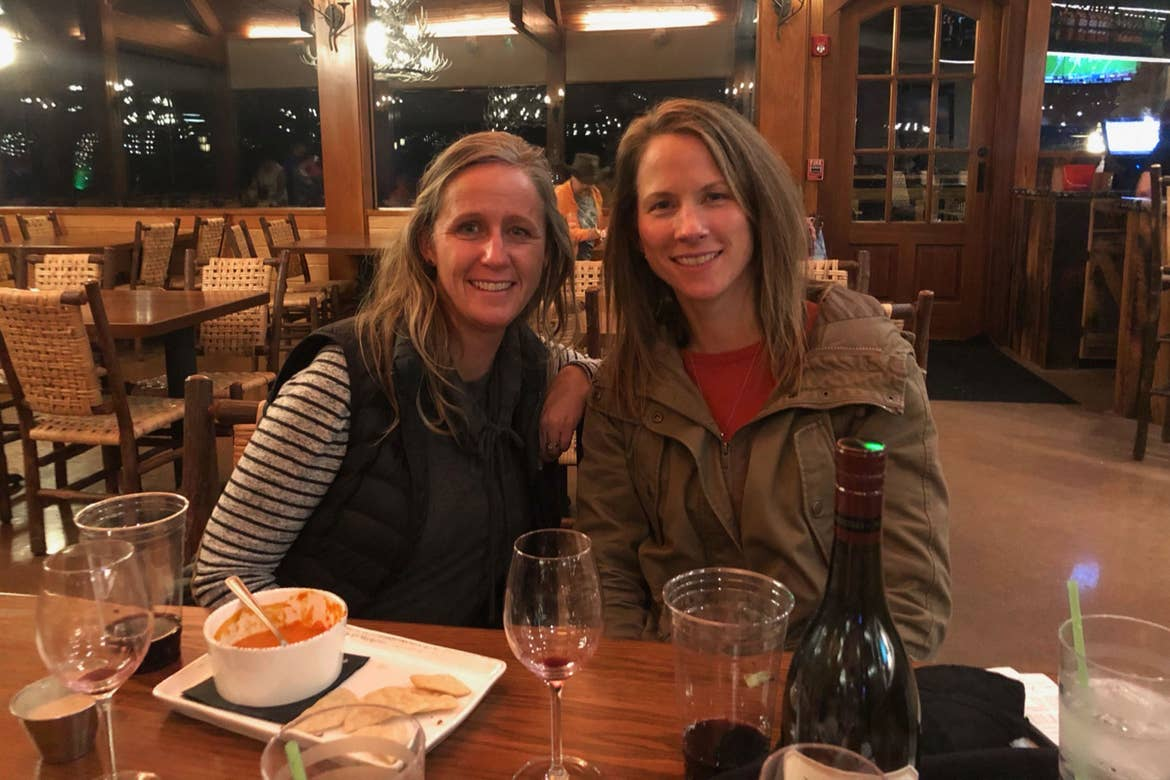 Featured Contributor, Jennifer C. Harmon's two girlfriends wear seated at a table wearing a striped shirt and utility jacket.
