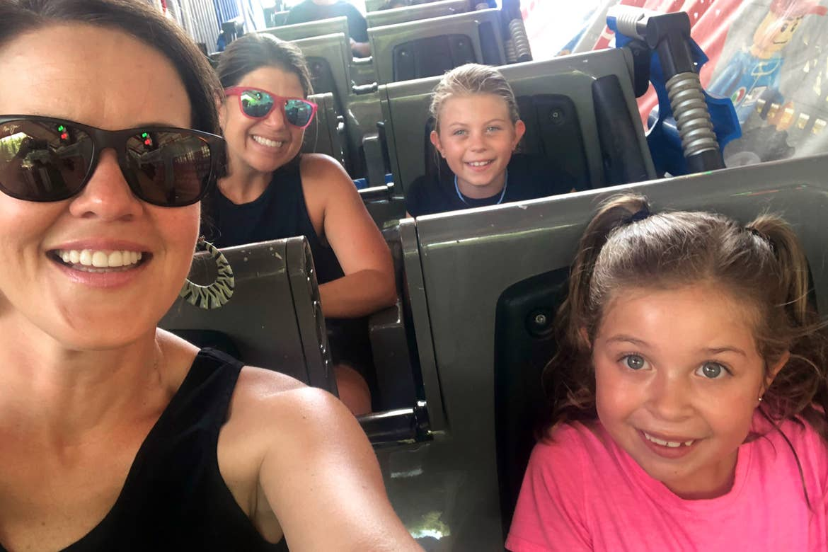 Two women (left) and two young girls (right) are seated on a roller coaster vehicle.