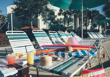 Outdoor seating with sun chairs and umbrellas in West Village at Orange Lake Resort near Orlando, Florida