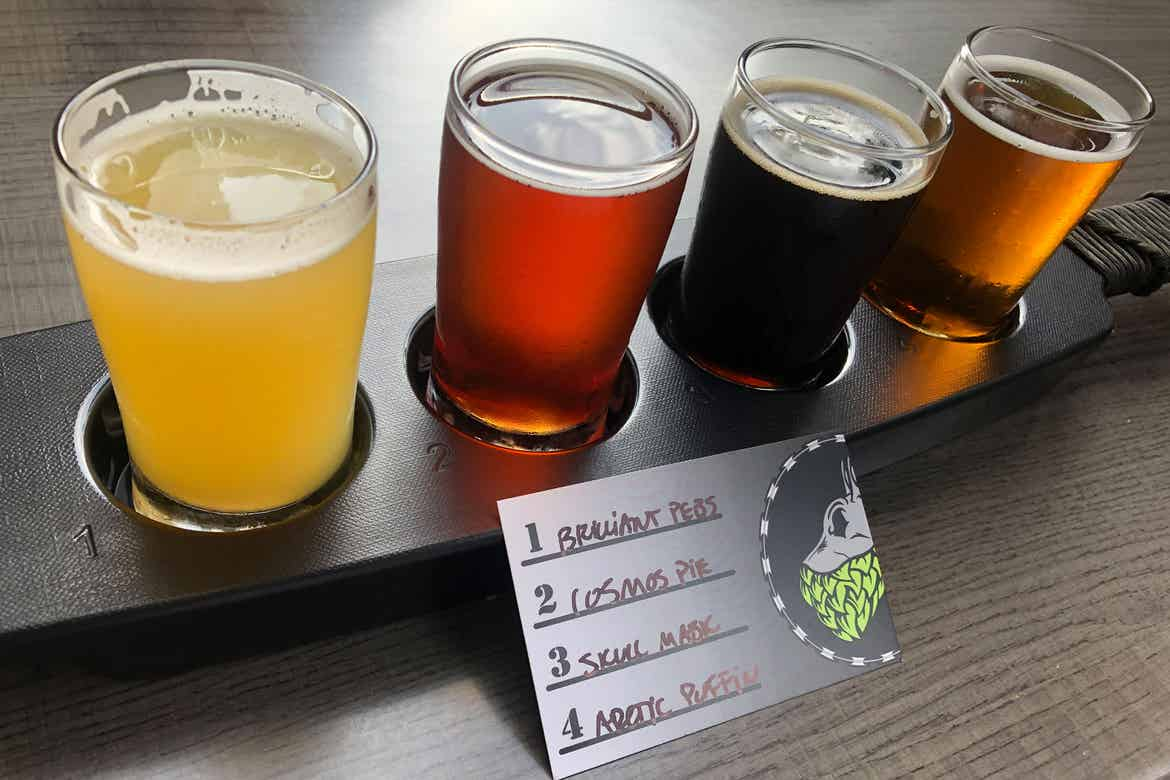 A beer flight with a label that reads, '1. Brilliant Pebs 2. Cosmos Pie 3. Skull Mask 4. Arctic Puffins' from 'Tactical Brewing Co.'
