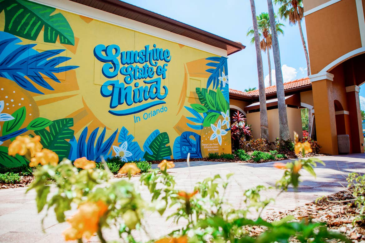 Some landscaping in the foreground passes over a large wall mural of a yellow sun surrounded by blue and green monsterra leaves that reads in blue, 'Sunshine State of Mind'  in North Village at Orange Lake Resort near Orlando, Florida