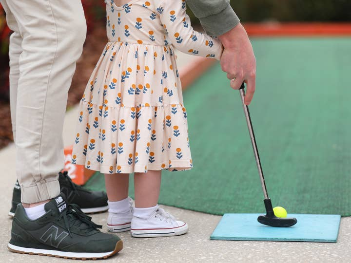 Child and adult playing mini golf.