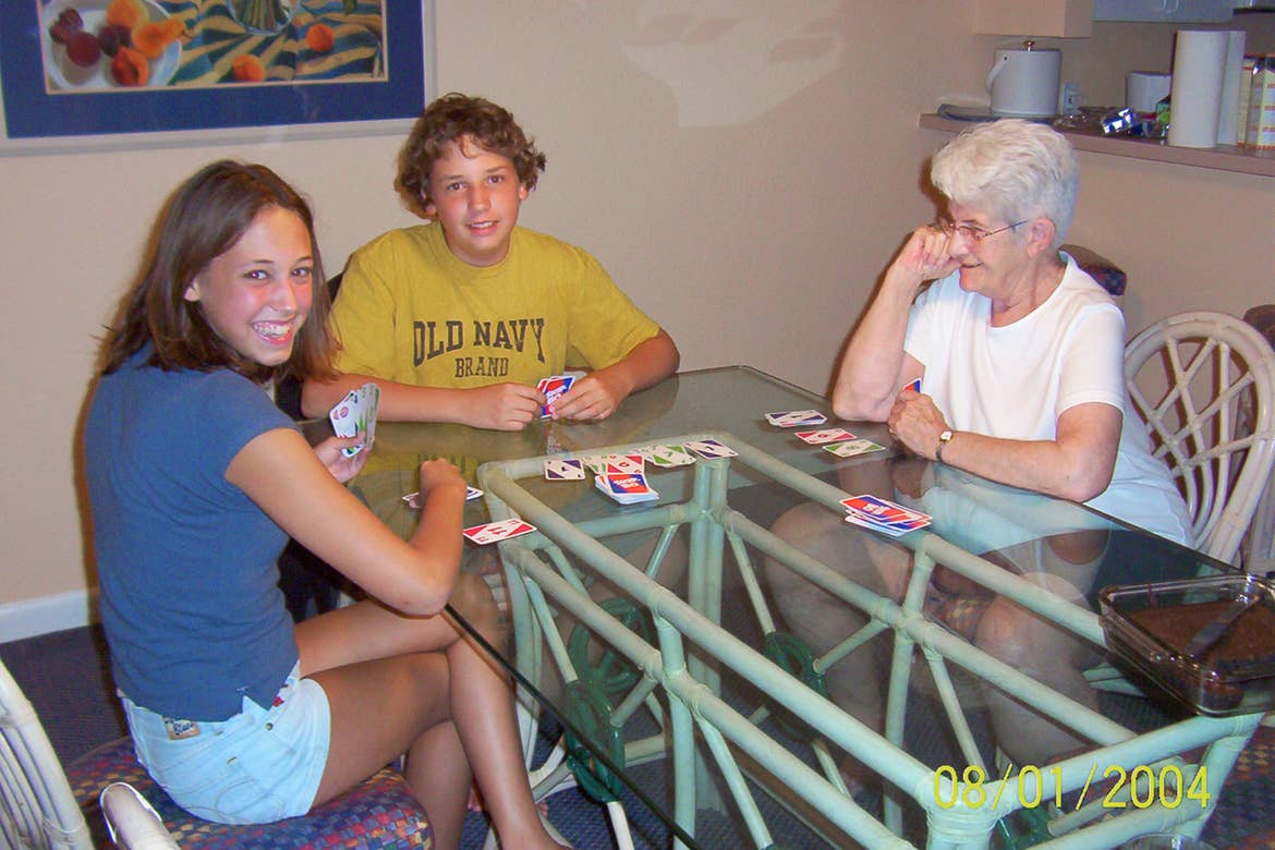 A caucasian teen boy (top-middle), a teenage girl (left) and an older woman (right) are seated at a table playing card games indoors.
