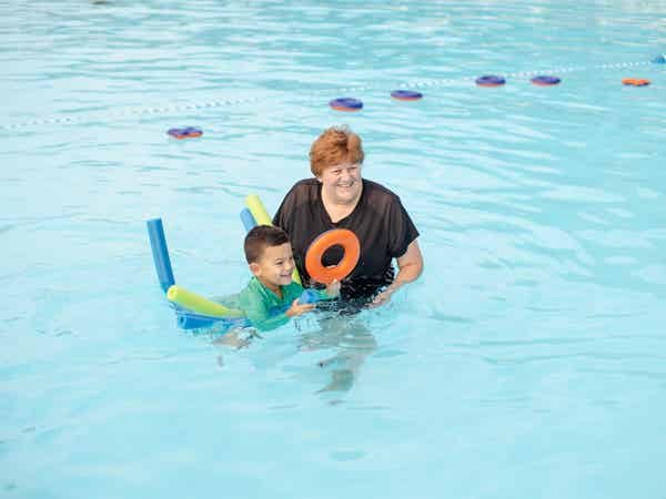 Woman helping child float on pool tubes in outdoor pool at Holiday Hills Resort in Branson, Missouri.