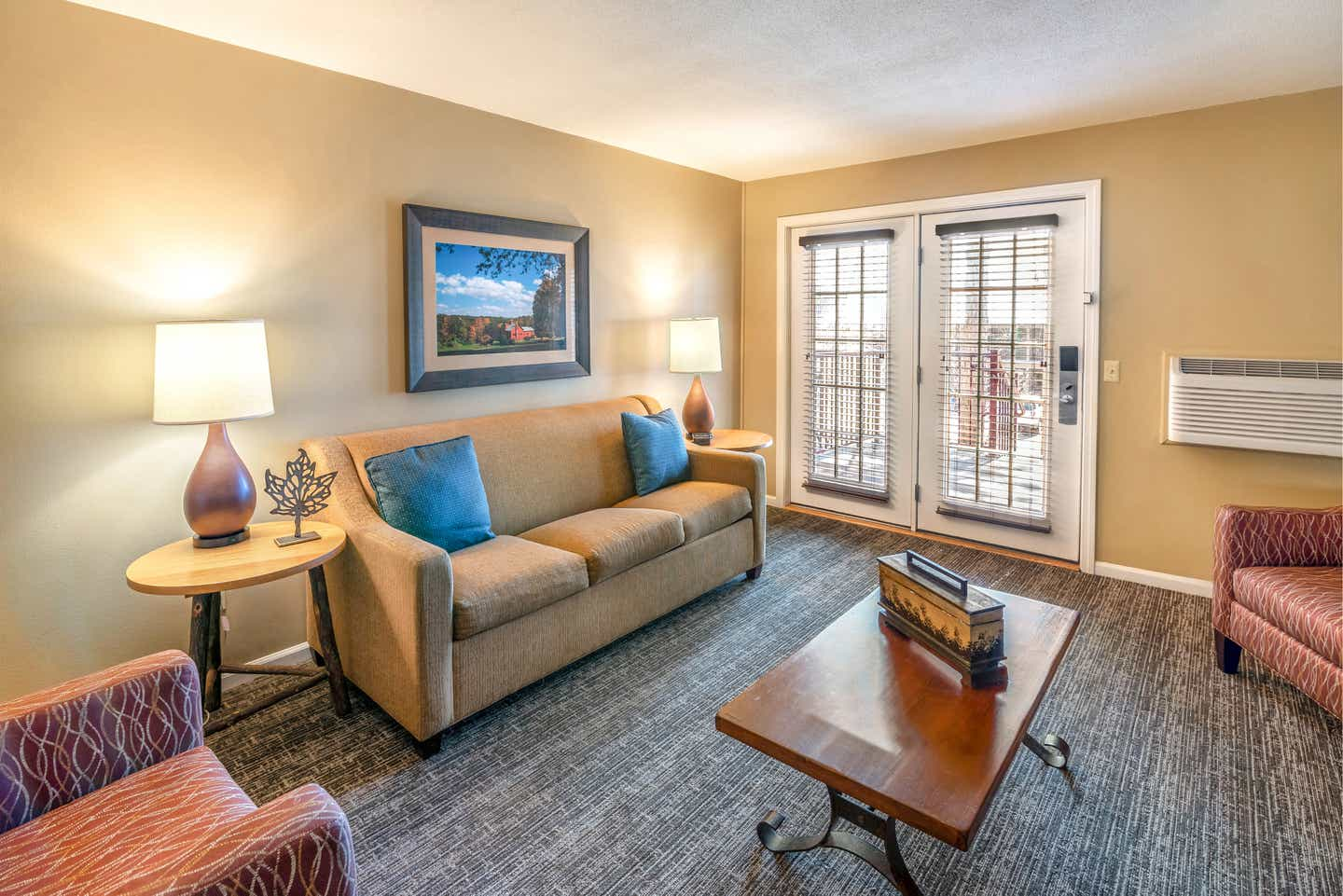 Living room with a sofa, two chairs, and tables in a one bedroom villa at Oak n' Spruce Resort in South Lee, Massachusetts