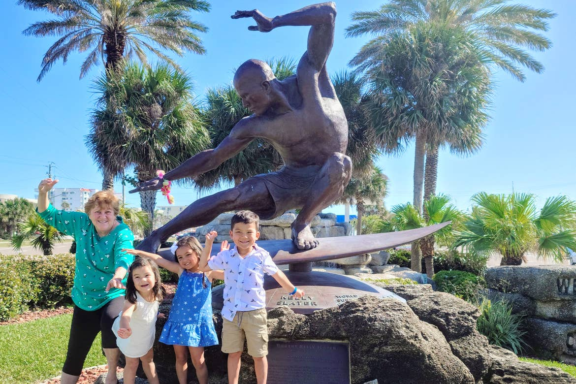 Featured Contributor, Angelica Kajiwara's mother and three children pose in front of a statue of Kelly Slater in downtown Cocoa Beach.