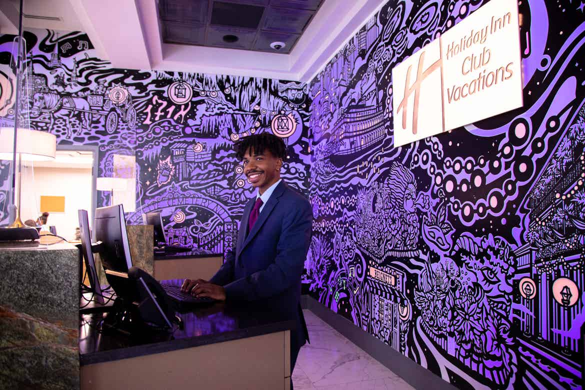 HICV Team Member, Ruben, stands in front of a mural with animated projection mapping in various colors of purple, orange, yellow and magenta featured in the lobby of our resort in New Orleans, Louisiana.