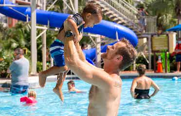 Featured Contributor, Sally Butan's husband holds their son, Alston, in the pool at our Orange Lake Resort located near Orlando, FL.