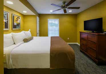 Bedroom with TV and dresser in a one-bedroom ambassador villa at the Hill Country Resort in Canyon Lake, Texas.