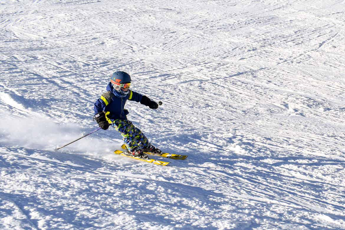 Contributor, Jessica Averett's son clad in winter and skiing gear ascends down the slopes.